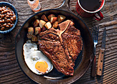 T-bone steak with fried egg and fried potatoes (top view)