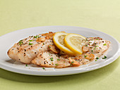 Tilapia fillets with garlic and lemon slices