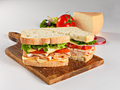 A sandwich with turkey breast, tomato, Munster cheese and salad, sliced