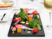 Decorative salad plate with ruccola, tomato and different types of beet
