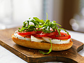 A baguette slice topped with mozzarella, tomatoes and rocket