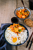 A bowl containing steamed rice, fried egg and kimchi