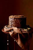 Glutenfreier Schokoladenkuchen auf Beistelltischchen vor braunem Hintergrund