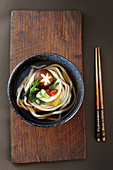 A bowl of udon noodle soup on a wooden board (Japan)