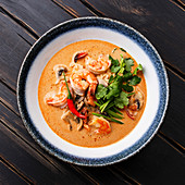 Tom Yam kung Spicy Thai soup with shrimp, seafood, coconut milk and chili pepper in bowl close-up