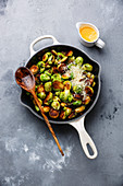 Fried Brussels sprouts with parmesan cheese in frying pan on concrete background