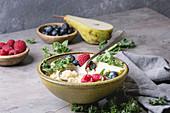 Vegan quinoa porridge with kale, strawberries, blueberries and sliced pear