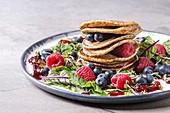 Vegane Kichererbsen-Pancakes auf Salat mit Rote-Bete-Blättern, Sprossen und Beeren