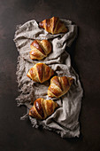 Fresh baked traditional croissant on linen cloth over dark brown texture background