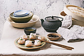 Asian steam potstickers dumplings stuffed by shrimps, served with soy sesame sauce, chopsticks, teapot, tea, bamboo steamer