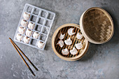 Frozen ready to cook asian potstickers dumplings stuffed by shrimps in plastic box with chopsticks and bamboo steamer over grey texture background