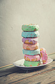 A stack of donuts on wooden table against the wall