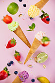 Sweet and colourful ice cream in waffle cones with sprinkles and ingredients falling or flying in motion against