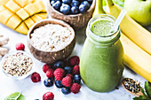 Close-up of green fresh smoothie with fruits, berries, oats and seeds, selective focus