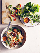 Vietnamese noodles with meatballs, spring rolls and herbs