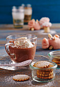 Hot Russian chocolate with vodka and cream, honey biscuits in a jar, and a marzipan pig