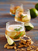Glasses of caipirinha punch with melon with party biscuits