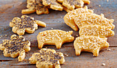 Spicy biscuits shaped like clover leaves and pigs with poppy seeds and sesame seeds