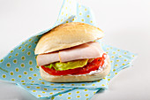 A sandwich with cream cheese, tomatoes, lettuce and turkey ham