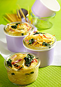 Colourful baked pasta nest with spinach, boiled ham and Parmesan