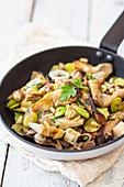 Oyster mushrooms, artichoke hearts and lima beans in frying pan