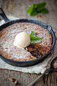 Chocolate chip cake with vanilla ice cream in a cast iron pan