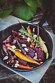Roasted beets and carrots with goat cheese in a cast iron pan