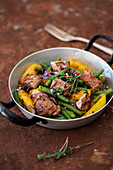 Steak with green beans, red onion, and potatoes in a pan