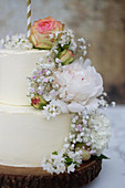 A two-tier wedding cake with butter cream and fresh flowers