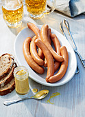 Sausages with beer tankards, a jar of mustard and bread