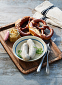 White sausages with pretzels and sweet mustard