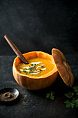 Pumpkin soup served in pumpkin with fresh parsley, cream and pepper