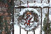 Weihnachtlich geschmückter Kranz verschneit am Gartenzaun