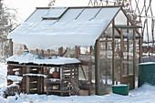 Gewächshaus mit Schnee im winterlichen Garten