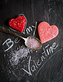 Chalk lettering 'Be my Valentine' with heart cookies and pink sugar