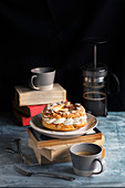 French paris-brest pastry, coffee mugs and french coffee pot on the table
