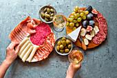 Zwei Vorspeisenplatten mit Wurst, Schinken, Käse und Obst dazu Wein, Oliven und Kapern