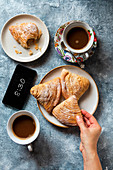 Female having breakfast, Italian sfogliatelle and coffee on the table