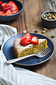Cake slice on blue plate with powdered sugar and strawberries