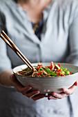 Frau hält eine Schüssel Soba-Nudeln mit Gemüse in den Händen