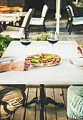 Mann und Frau mit Gemüsepizza und Rotwein an Restauranttisch im Freien
