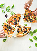 People s hands taking freshly baked Italian vegetarian pizza with vegetables and fresh basil over white marble table, top view