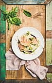 Summer salad with smoked turkey ham and pear in white plate over rustic wooden background