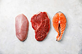 Raw food turkey breast, beef meat and Salmon oily fish steak on white textured background