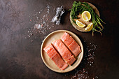 Sliced raw uncooked salmon fillet on ceramic plate with green dill, lemon, salt, pepper over dark brown texture background