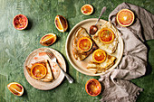 Homemade crepes pancakes served in ceramic plates with bloody oranges and rosemary syrup with sliced sicilian red oranges over green texture background
