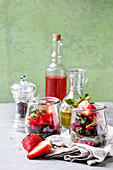 Beetroot and strawberry salad served with arugula and nuts in glass jars with cloth, pepper and bottles of fruit ocet and olive oil over grey table with green wall as background