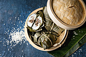 Asian rice piramidal steamed dumplings from rice tapioca flour with meat filling in banana leaves served in bamboo steamer with rice