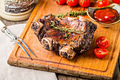 Delicious barbecued ribs seasoned with a spicy sauce and served with beer, seasonings, tomato and ketchup on an old rustic wooden chopping board