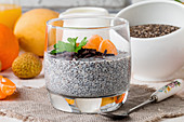 Chia seed pudding with mangoes and tangerines on glass cup for breakfast on white background